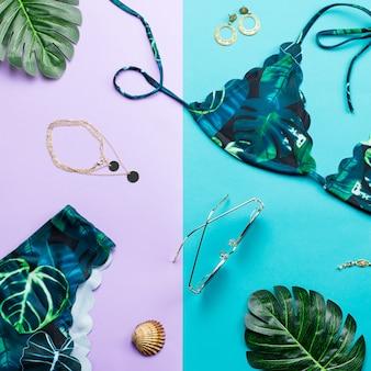 トロピカルビキニ水着、ビーチファッション。旅行者の女性のアクセサリーフラットは水着、ヤシの葉で横たわっていた。