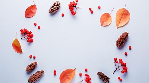 秋のフレーム、葉、ナナカマドの果実、オレンジ色のカボチャ、パステル調の背景に松ぼっくり