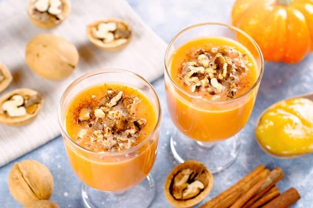 Здоровый тыквенный смузи с грецкими орехами и корицей в очках на деревенском фоне