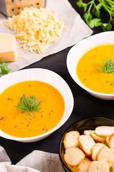 Тыквенный крем-суп с гренками и свежим укропом и петрушкой на темном деревянном фоне, вид сверху