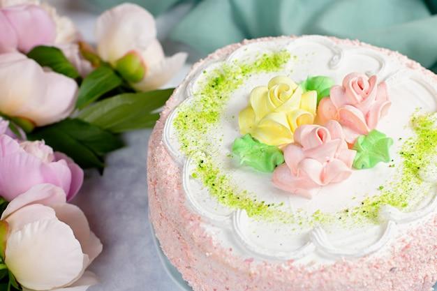 Красивый вкусный торт украшенный цветами в пастельных тонах на деревянный стол с пионами, вид сверху