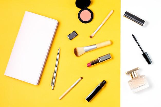 日記、化粧品、黄色の背景に香水とフェミニンなデスクワークスペース