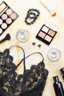 Черное кружевное белье с косметическими средствами, косметикой для макияжа, украшениями черного и золотого цвета. модная планировка, вид сверху