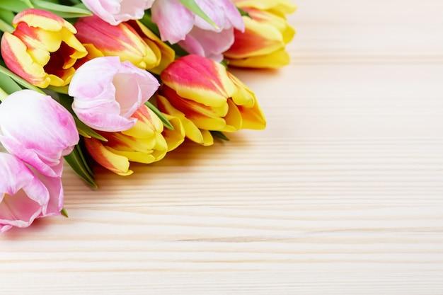 Красные и розовые тюльпаны на деревянном столе крупным планом, копией пространства