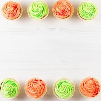 Вкусные красочные кексы крупным планом на белом деревянном столе, вид сверху