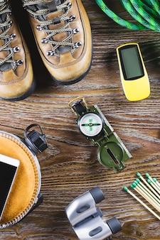ハイキング、旅行用具、ブーツ、コンパス、双眼鏡、木製テーブルのマッチ。アクティブなライフスタイルのコンセプト