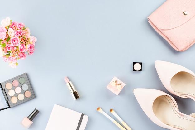 Мода блогера рабочего пространства плоская планировка с насосами, косметикой, кошельком, ежедневником и цветами.