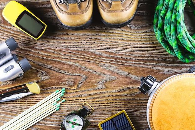 ハイキング用品、ブーツ、コンパス、双眼鏡、マッチ、木製テーブルのトラベルバッグ。アクティブなライフスタイルのコンセプト。