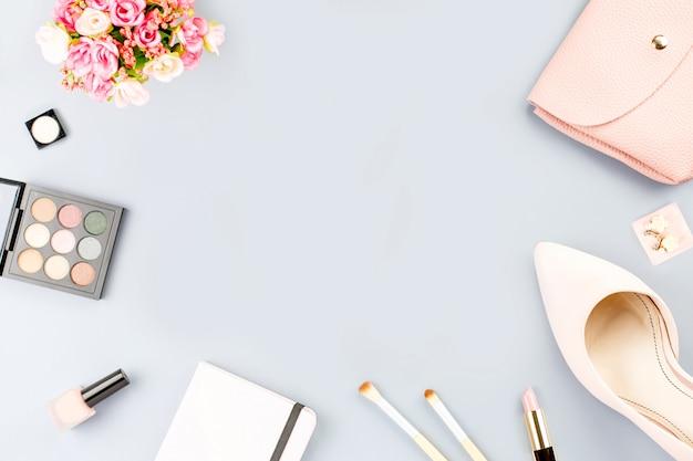 フラットのファッションブロガーワークスペースには、ポンプ、化粧品、財布、プランナーの本、花が横たわっていた。