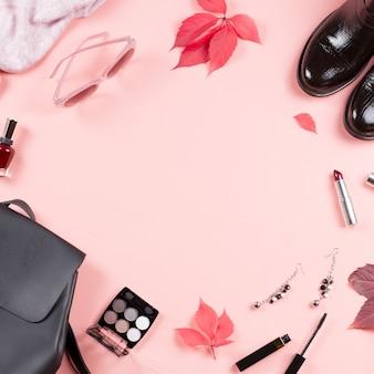 秋の女性服コレクション。女性はファッションコンセプトフラット横たわっていた。バックパック、ブーツ、スカーフ、化粧品のオーバーヘッド