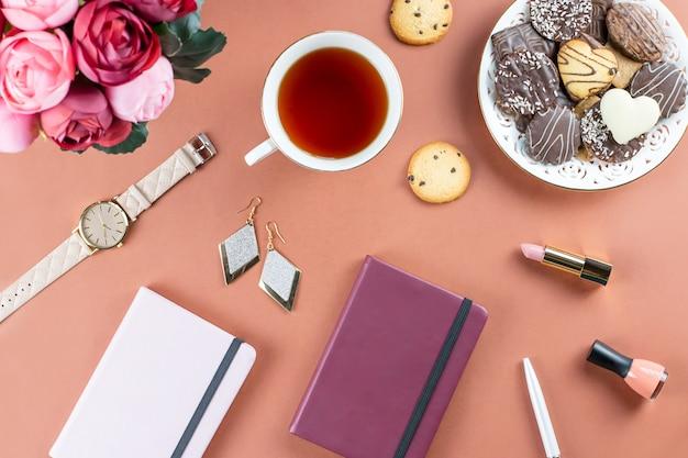 フラットレイアウトのホームオフィスデスク。日記、花、お菓子、ファッションアクセサリーのあるフェミニンなワークスペース。ファッションのブロガーのコンセプトです。