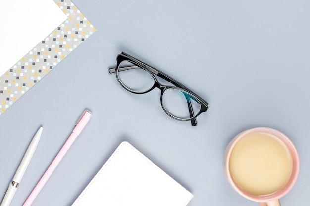 フラットレイアウトのホームオフィスデスク。メモ帳、眼鏡、マグカップ、日記、植物と女性のワークスペース。コピースペース