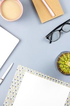 フラットレイアウトのホームオフィスデスク。プランナー、眼鏡、お茶のマグ、日記、植物と女性のワークスペース。コピースペース