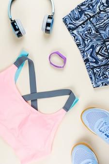 中立的なテーブルの女性スポーツ服、スニーカー、ヘッドフォン、フィットネストラッカー。スポーツファッションのコンセプトです。フラットレイ