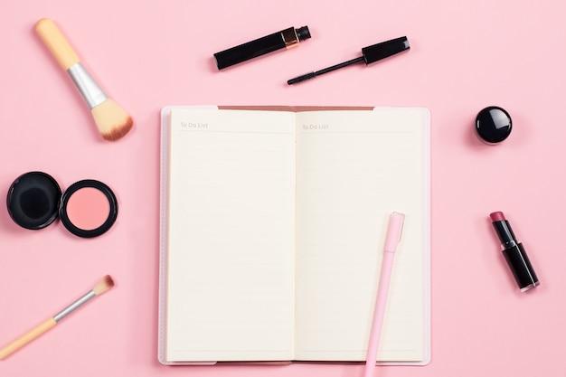 美容ブロガーのオブジェクトはフラットレイアウトです。美容製品とパステルピンクの背景にスタイリッシュな女性のアクセサリー