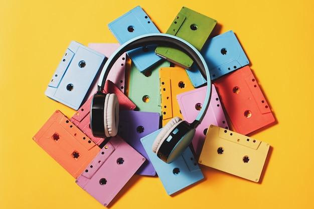 明るい黄色の表面に塗装されたオーディオカセットと青いヘッドフォン