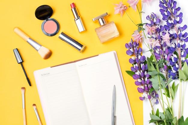 現代の女性のアクセサリー。美容製品、メモ帳、アクセサリー、パステル調の背景の花