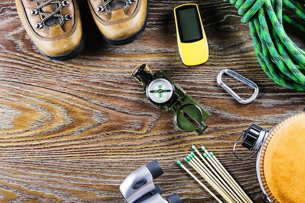 ハイキング、旅行用具、ブーツ、コンパス、双眼鏡、木製の背景と一致します。アクティブなライフスタイルのコンセプト。