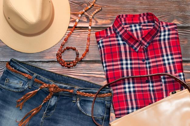 赤いチェックシャツ、ジーンズ、革の帽子、バッグ、ベルト