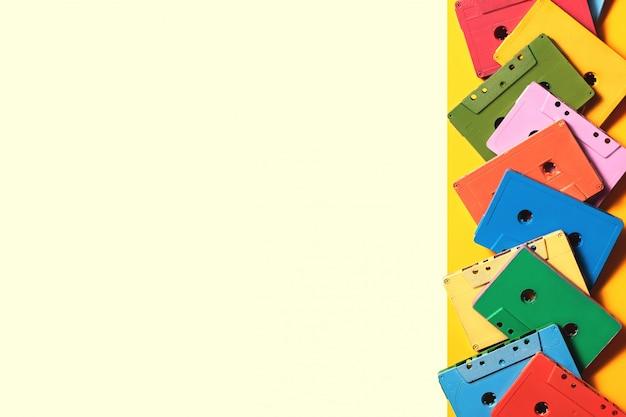 明るい黄色の背景、コピースペース、上面に塗装済みオーディオカセットフレーム。レトロな音楽的背景
