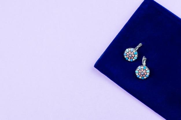 パステル調の背景にピンクとブルーの色の女性のスタイリッシュなイヤリング。