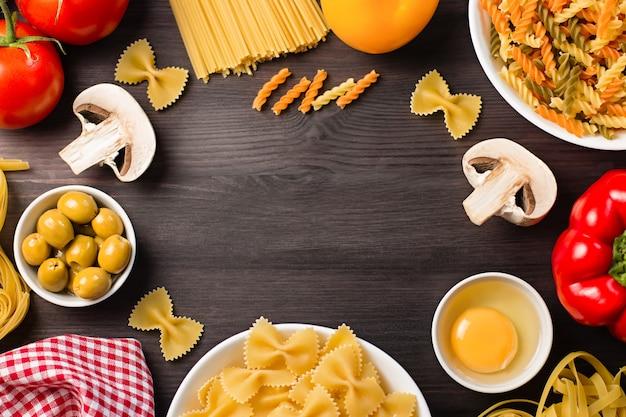 さまざまなパスタ、野菜、キノコ、オリーブのイタリア料理の食材のフレーム。暗い背景の木にフラットレイアウト