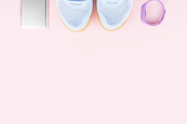 紫の女性のスニーカー、フィットネストラッカー、ピンクの背景のスマートフォン。フラット横たわっていた、スペースをコピーします。