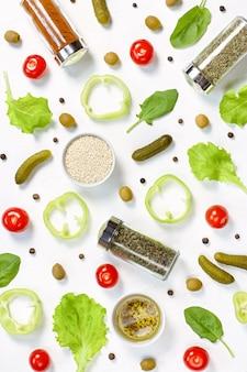 白い机の上のサラダ食材のレイアウト。チェリートマト、きゅうり、野菜、コショウ、スパイスと食品パターン