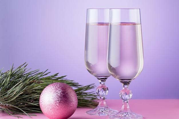 Рождественская открытка с двумя бокалами шампанского, рождественские украшения, ветка ели в розовых тонах. копировать пространство