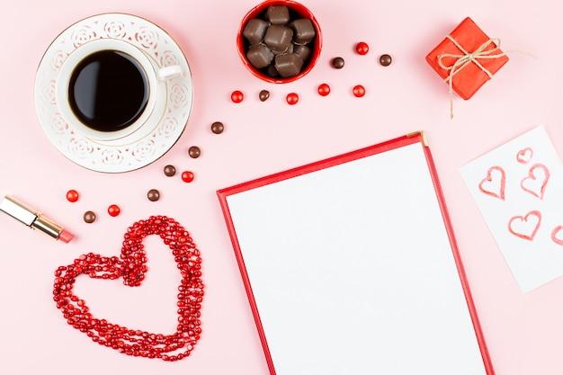 Шоколадные конфеты, горячий напиток, губная помада, лист бумаги, подарочная коробка. женственный фон в красных и белых тонах.