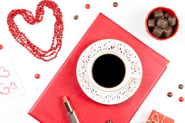 Кофейная чашка, конфеты, губная помада, форма сердца и подарочная коробка на белой поверхности. женский день концепция плоской планировки.