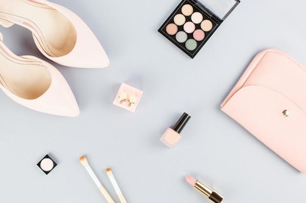 Плоская планировка с помпами, косметикой, сумочкой, ежедневником и цветами.