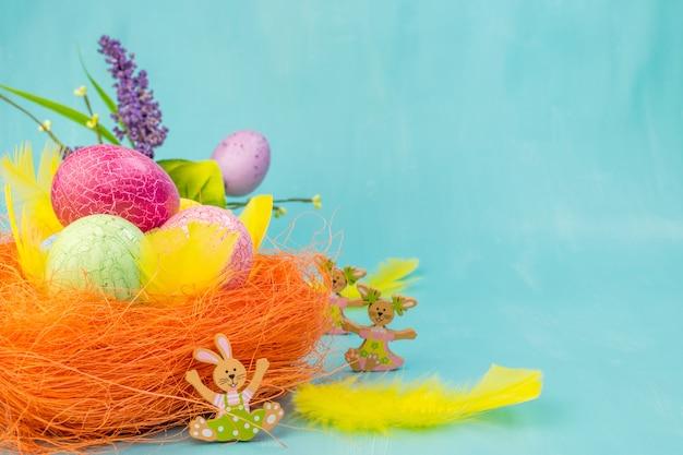 Вид спереди красочные пасхальные яйца в оранжевом гнезде с весенними цветами и желтыми перьями на бирюзовом фоне с пространством сообщений