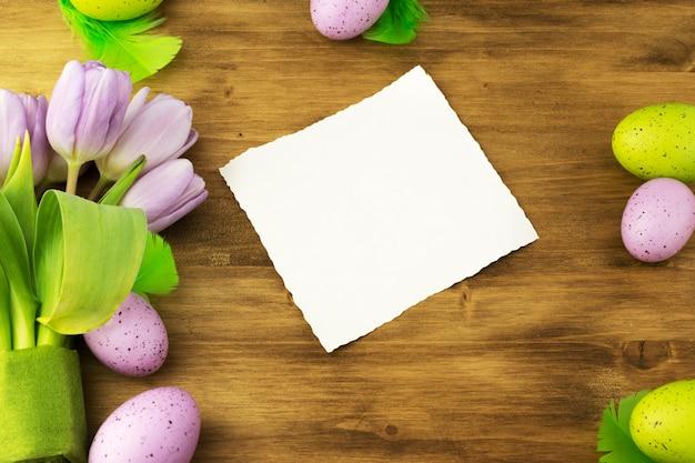 茶色の木製の背景にカラフルなイースターエッグ、紫のチューリップ、緑の羽、メッセージカードの平面図です。