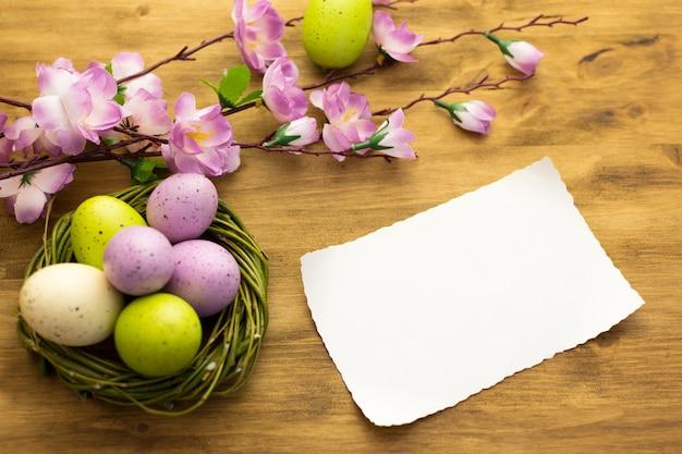茶色の木製の背景に柳の巣、春の花、メッセージカードでカラフルなイースターエッグの平面図です。