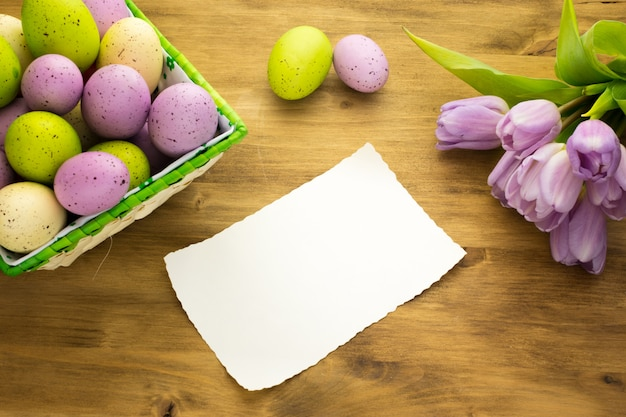 茶色の木製の背景にバスケット、紫のチューリップ、メッセージカードでカラフルなイースターエッグの平面図です。