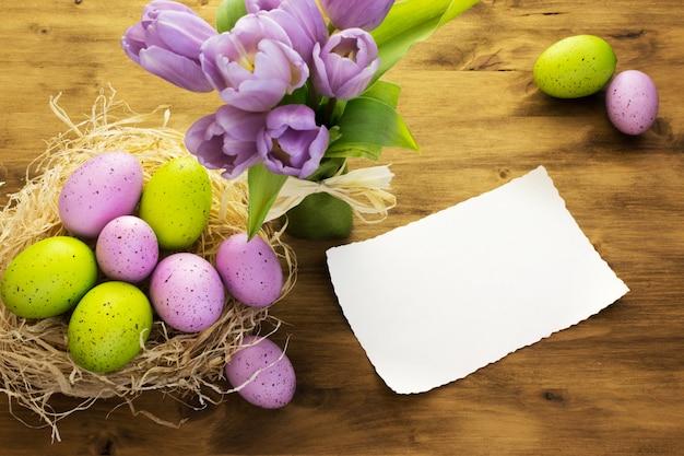 茶色の木製の背景に巣、紫のチューリップ、メッセージカードでカラフルなイースターエッグの平面図です。