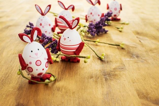 茶色の木製の背景にカラフルなイースターのウサギの卵と春の花の正面図。