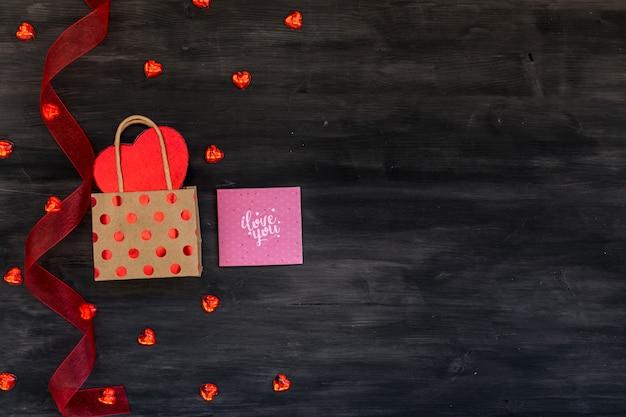 ギフト用の箱、異なる心、グリーティングカード、暗い背景の木に赤いリボンとバレンタインの日のシーン。
