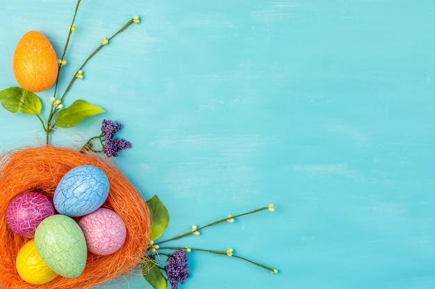 Вид сверху красочные пасхальные яйца в оранжевом гнезде и весенние цветы на бирюзовом фоне с пространством сообщений
