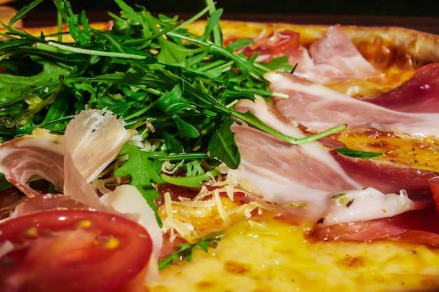 ハム、トマト、ハーブ、木製テーブルの上のイタリアのピザ