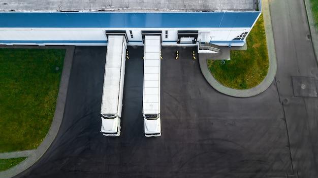Грузовые автомобили загружаются в современный логистический центр. с высоты птичьего полета.