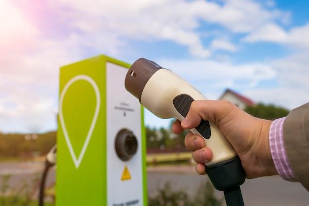 Электрический автомобиль зарядный кабель в мужской руке крупным планом