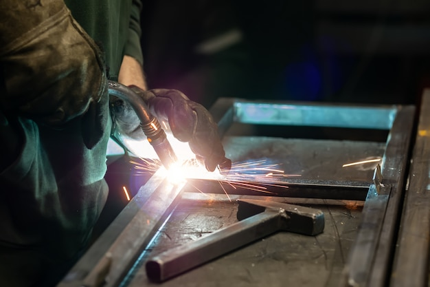 Сварщик готовит раму. сварщик готовит металл. сварщик готовит металлические конструкции. сварочные работы искры, расплавленный металл