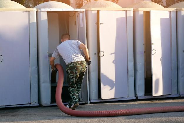 Работник чистит уличные туалеты, откачивает сточные воды