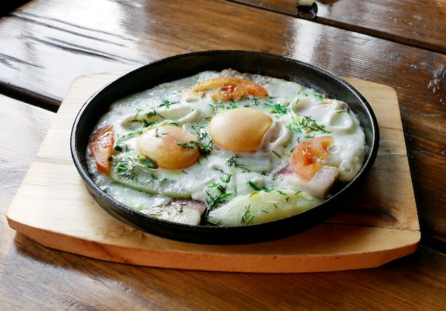 Яичница с беконом и луком на сковороде. домашняя еда