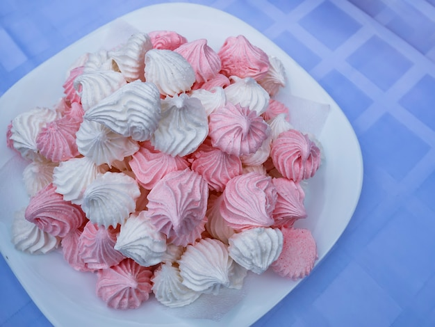 Розовый зефир в тарелку крупным планом