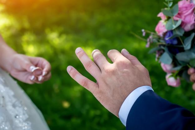 Обмен обручальных колец на свадьбу, руки крупным планом