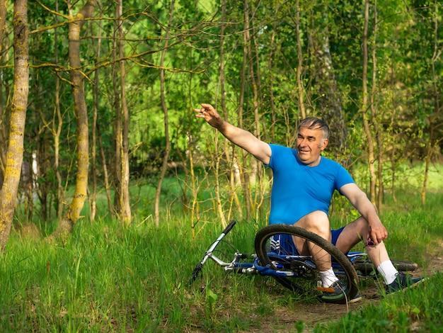 Пожилой мужчина машет рукой на велосипеде
