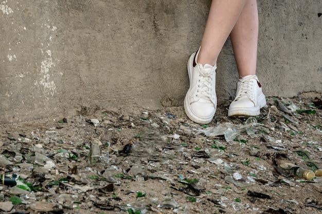 壊れたガラスと破片の山の中のティーンの足。問題を抱えた十代の若者たち